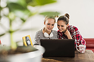 Two female friends using laptop at home - UUF002740