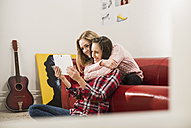 Two female friends using digital tablet at home - UUF002763
