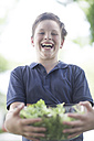 Portrait of a laughing boy holding a bowl of salad - ZEF002747