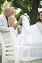 Woman setting a table outside with husband surprising her with a kiss - ZEF003441