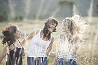 South Africa, Girl friends dancing and jumping in field - ZEF002772