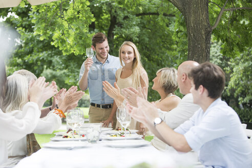 People clapping hands for young couple on a garden party - ZEF003474
