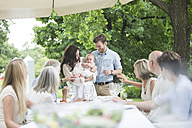 Baby being introduced to family on a garden party - ZEF003475