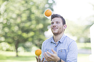 Young man juggling with oranges outdoors - ZEF003499