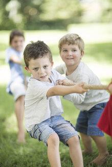 Kids in garden playing tug of war - ZEF002827