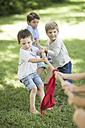 Kids in garden playing tug of war - ZEF002828