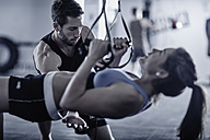 Fitness trainer keeping time with woman doing pull-ups - ZEF002619