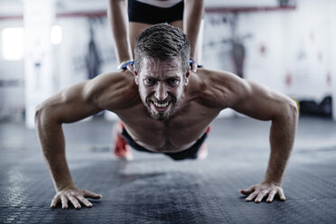 Man doing push-ups with woman kneeling on his back - ZEF002624