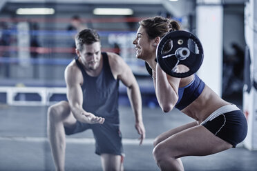 Trainer watching woman doing fitness training with weights - ZEF002628
