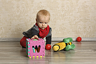 Baby girl with motor skill toy on floor - SHKF000046
