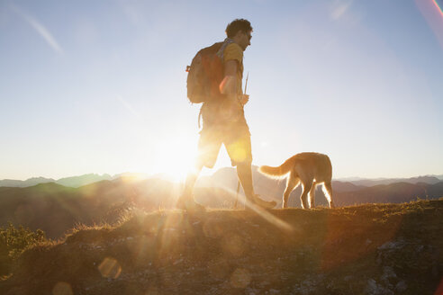 Austria, Tyrol, Unterberghorn, hiker with dog at sunrise - RBF002098