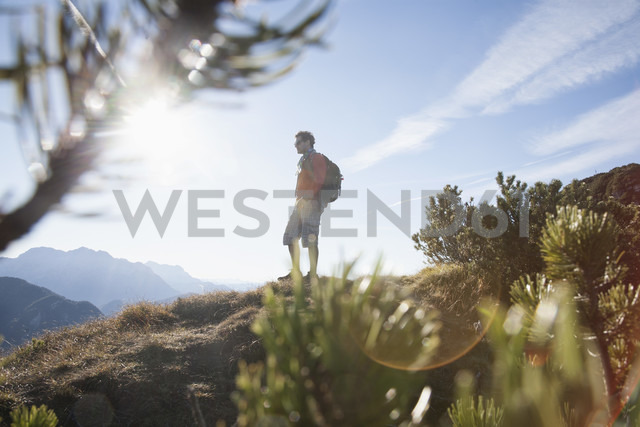 Austria, Tyrol, Unterberghorn, hiker at sunrise - RBF002095