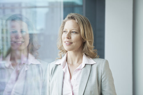 Businesswoman in office looking out of window - RBF002108