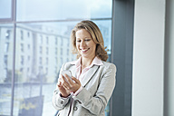Smiling businesswoman using cell phone in office - RBF002114