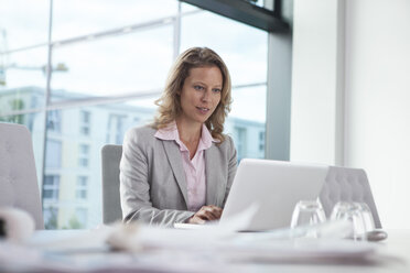 Businesswoman using laptop in conference room - RBF002109