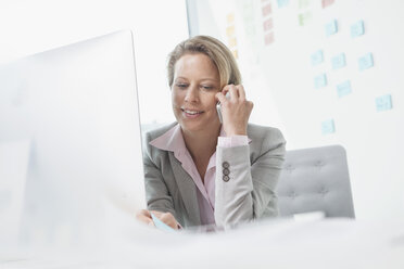Smiling businesswoman on the phone in office - RBF002143