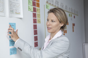 Businesswoman in office at wall with adhesive notes - RBF002136