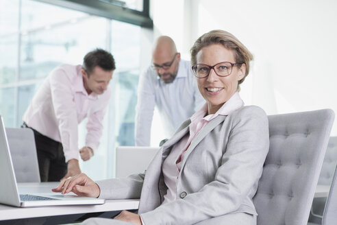 Three businesspeople with laptop in conference room - RBF002154