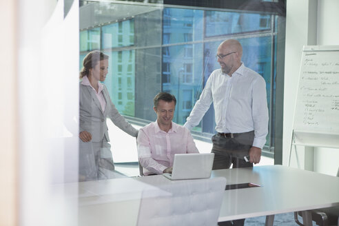 Three businesspeople with laptop in conference room - RBF002160