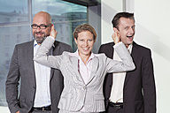 Businesswoman pulling ears of colleagues - RBF002155