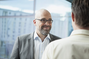 Businessman smiling at colleague in office - RBF002166