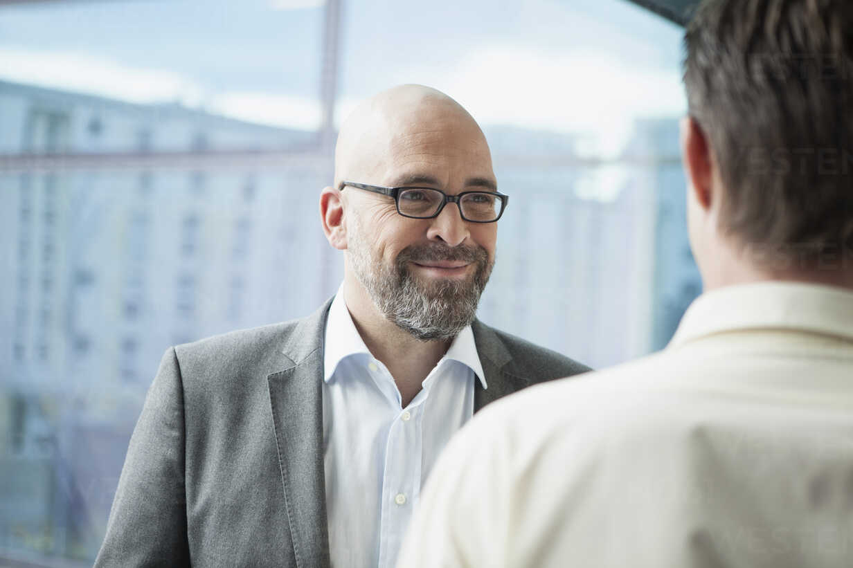 Businessman smiling at colleague in office - RBF002166 - Rainer Berg/Westend61