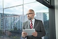 Businessman at the window with digital tablet - RBF002176