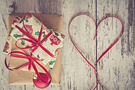 Stack of Christmas presents, red Christmas bauble and ribbon shaped like a heart on wood - SARF001152