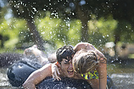 Young couple on holiday having fun with inner tube in a pool - ZEF003295