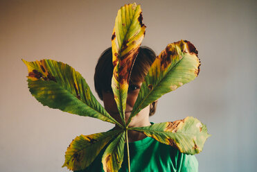 Boy with leaf in front of face - ZM000351
