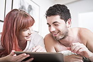 Young couple lying in bed using digital tablet - ZEF002928