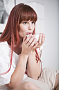 Woman sitting on bed holding healthy tea in a small bowl - ZEF002932