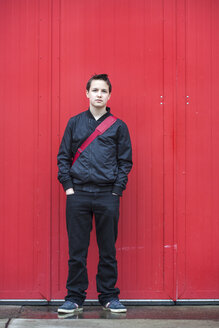 Portrait of serious looking teenage boy with hands in his pockets in front of red door - MVC000152