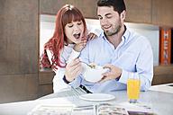 Couple in kitchen having breakfast with orange juice and muesli - ZEF002641