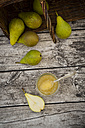Whole and sliced organic pears and glass of pear jam on grey wood - LVF002469