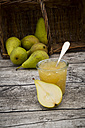 Whole and sliced organic pears and glass of pear jam on grey wood - LVF002470