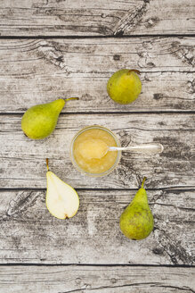 Whole and sliced organic pears and glass of pear jam on grey wood - LVF002472
