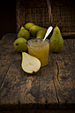 Whole and sliced organic pears and glass of pear jam on dark wood - LVF002473