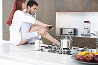 Couple in kitchen sharing an intimate moment - ZEF002657