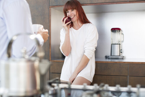 Happy couple in kitchen with apple and cup of coffee - ZEF002659
