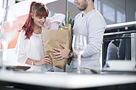Couple in kitchen unpacking groceries - ZEF002665