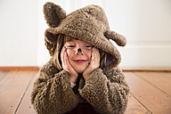 Portrait of happy little girl masquerade as a bear lying on wooden floor - LVF002452