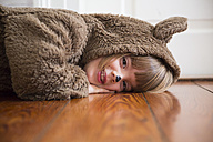 Portrait of smiling little girl masquerade as a bear lying on wooden floor - LVF002455
