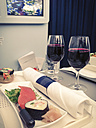 Sushi and sashimi appetizer with wine in business class of airplane - ABAF001588