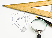 Drawn lightbulb, set square, magnifier and ballpen on white paper - AMF003443