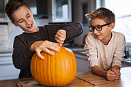 Two boys preparing a big pumpkin for Halloween lantern - PAF001096