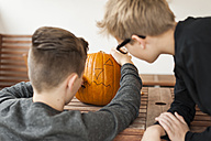 Two boys preparing a pumpkin for Halloween lantern - PAF001097