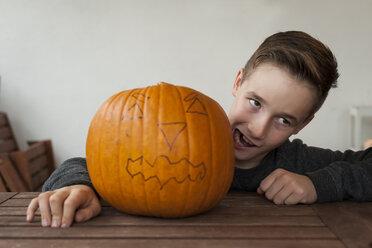 Boy making a face beside big Halloween pumpkin - PAF001099