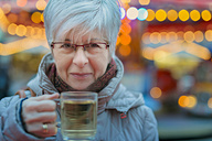 Senior woman holding glass of mulled wine - FRF000149