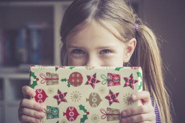 Little girl holding Christmas present - SARF001161